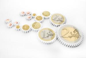 Mehrere Euro-Münzen mit Zahnkränzen, die ineinander greifen.