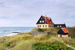 Ein dänisches Haus auf einer Anhöhe nahe eines Strandes.