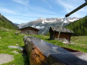Blick auf einen Holzbrunnen, in dessen Hintergrund Almhütten stehen.