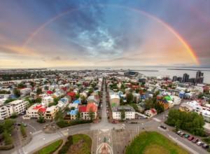 Foto von Reykjavik mit Regenbogen am Himmel.