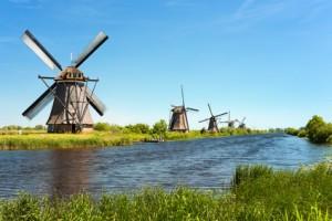 Windmühlen auf einer Wiese mit Wasser.
